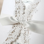 White satin lace tied in a knot, securing a white card with intricate lasercut in floral design, ivory insert card