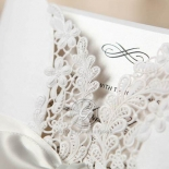 Elegant symbol in raised ink printing, ivory insert card, enclosed in a white gatefold invite with floral lasercut design with ribbon