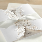 Knotted white satin lace wrapped around a matte white card with floral and leaf lasercut detail, ivory insert card