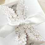 Intricate lasercut details on a white gatefold sleeve, bound by a satin lace tied in a knot, insert card with raised ink printing
