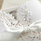 Zoomed in photo of the laser cut flower pattern on the sleeve of the white invitation