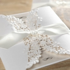Knotted silky smooth white satin lace, wrapped around a matte white gatefold invite with lasercut details, ivory insert card