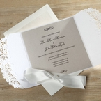 Unfolded white laser cut invitation featuring cream insert and embossed ink; ribboned