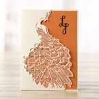 White laser cut peacock invitation with orange inner paper and raised ink printing