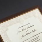 Embossed pearl paper, swirl detail, black raised lettering, gold and brown border