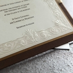 Chocolate brown hard layer with gold trim and ribbon, white inner paper featuring embossed swirl design