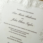 Matte white paper with raised ink lettering framed with Victorian swirl embossing