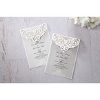 Intricate white lasercut flap with crystal stud, draped on a light grey pearlised card, set on a white backing paper