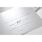 Raised ink fonts in calligraphic writing printed on a pearlised card stock in light grey