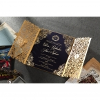 Open sleeved golden laser cut invite with hot foil stamped borders and calligraphic writing on a navy blue card