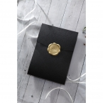 A closed pocket invite, sealed with a shiny gold wax stamp, pearlised card stock in charcoal black