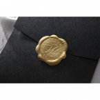 An elegant wax stamp in gold colour, stamped on the flap cover of a shiny black pocket invite