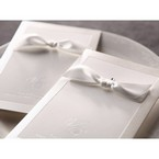 White ribboned, jeweled, hand assembled detail, silkscreened border detail, folded wedding invite