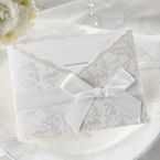 White bow and lace around a silk screened pocket invite with floral designs, smooth inner card stock