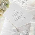 Floral silver design on a white pocket invite, wrapped with a silky smooth ribbon, and a white insert card