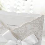 White insert card with embossed border, white pocket invite with floral design, smooth satin ribbon and lace