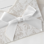 Classic white ribbon wrapped around a pocket invite with silver floral designs, inner card with embossed frame
