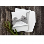 A white pocket invite with silver foiled text, wrapped with a silver bow along with its white envelope with pearl lining