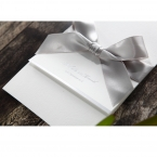 Silver foiled writing on the flap cover of a white lightly textured card, adorned with a satin ribbon