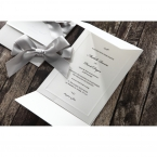 Matte white card with black raised ink writing, inside the white pocket with a shiny silver ribbon