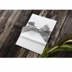 Zoom out view of a white pocket invite wrapped with a shiny silver bow, printed in silver foil