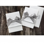 Lightly textured white card with a silver ribbon wrapped around, together with an envelope with printing on the flap