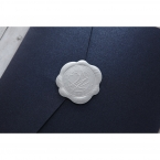 Stunning silver wax stamp seal with pre printed text and letter, sealing the shiny dark blue pocket invite