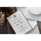 Golden emblem logo on a lightly textured white card, with the pocket with satin ribbon