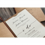 Brown craft card, enclosing a white textured card printed in raised ink, adorned with a lace wrapped center